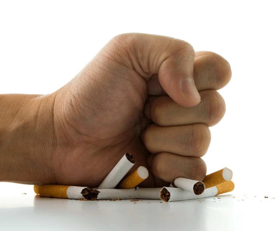Hand crushing a pile of cigarettes
